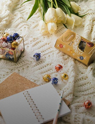 Cream notebook with tulips and a box of assorted Lindor.