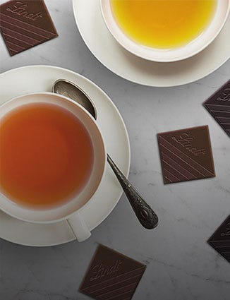 Cups of tea paired with squares of Lindt Excellence.