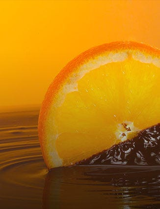 Slice of orange dipped in melted dark chocolate.