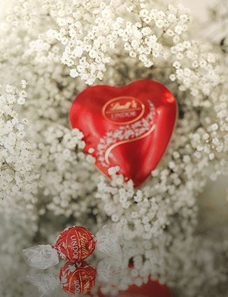 Romantic heart-shaped Lindor box surrounded by white flowers.